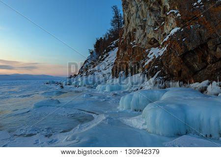 Huge icicles near rocks at sunrise. Beautiful winter landscape in the Lake Baikal.