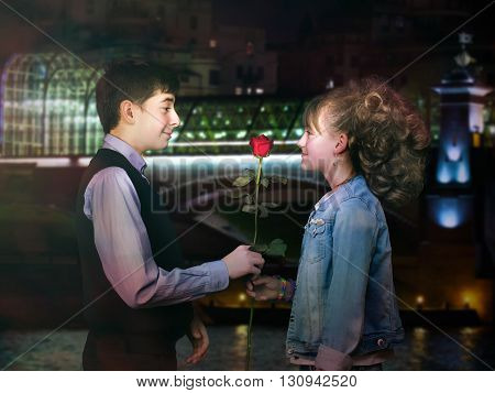 The boy gives a girl a flower - red rose. Background night city.