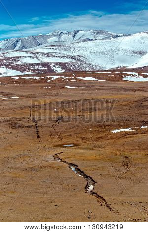 Snowy mountains. crack after an earthquake. Severe mountains peaks covered by snow. Russia Siberia Altai mountains Chuya ridge.