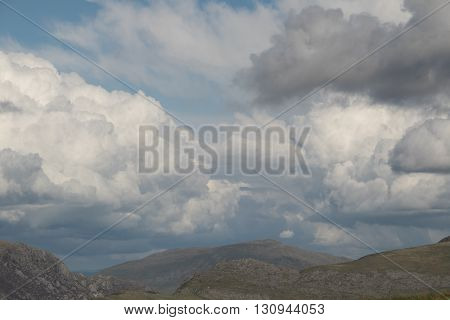 A rough rocky landscape with a hill in the distance under a moody sky with bulbous clouds.