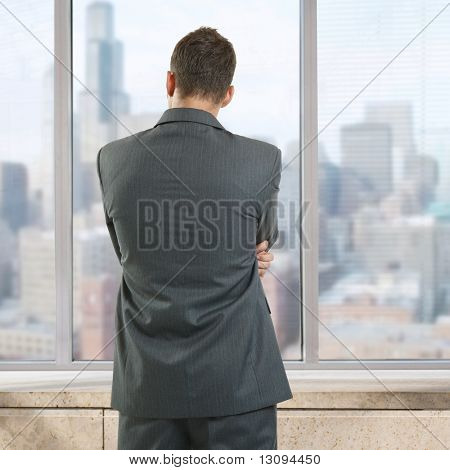 Businessman thinking in office, looking out of windows to downtown vista.