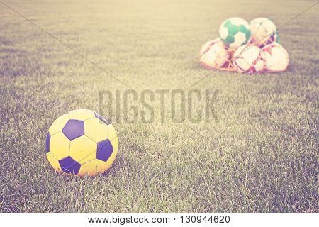 Retro filtered soccer balls on grass, shallow depth of field.
