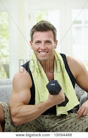 Muskulöse Mann sitzt auf dem Sofa zu Hause, Übungen mit Hand Langhantel.