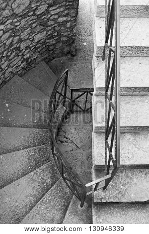 The circular staircase in the tower with iron railing. View from above.