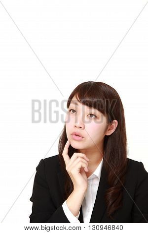 portrait of young Japanese businesswoman thinks about something on white background