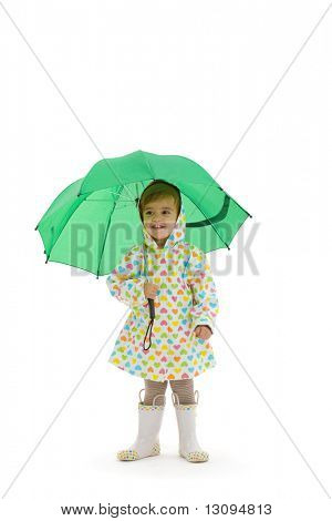 Happy small girl wearing raincoat and boots, holding green umbrella. Isolated on white background.