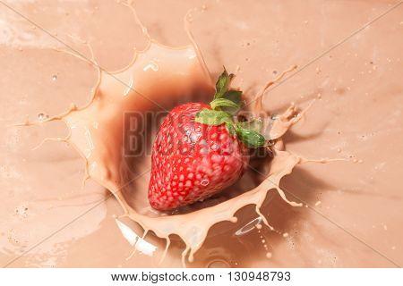closeup of strawberry falling into chocolate milk
