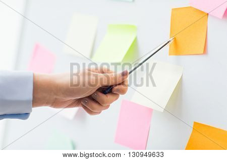 office, business, people and education concept - close up of hand with pen pointing to blank sticker on white board
