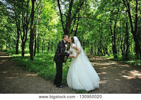 Groom Kissing Bride At V- Like Crossroads In Forest