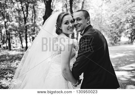 Fashionable Wedding Couple Looking Back Smiling. B&w Photo