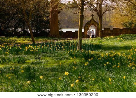 NEWSTEAD ENGLAND - MARCH 25: Two young caucasian adults approx 20-30 years old hold hands on a romantic walk in the gardens. At Newstead Abbey Newstead Nottinghamshire England. On 25th March 2016.