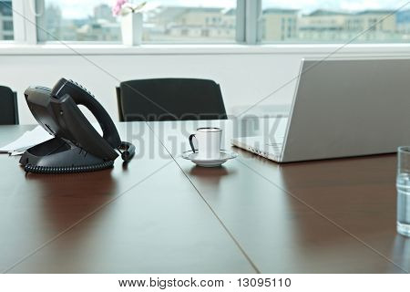 Phone, laptop compuer and coffee cup on office desk.
