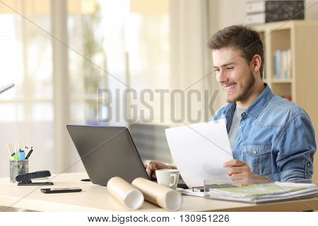 Entrepreneur working with a laptop and holding a document in a little office or home