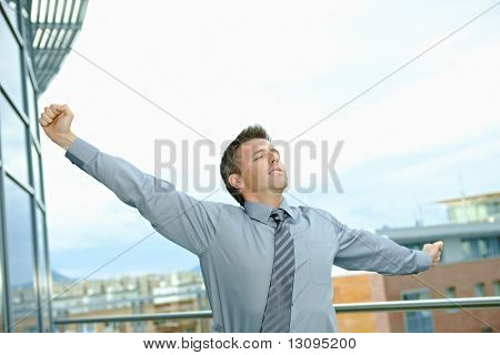 Businessman having break at office stretching arms outdoor on terrace.