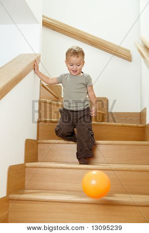 Happy little boy going down stairs after orange ball.