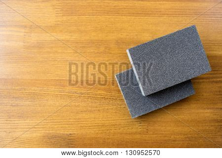 Sanding sponge on polishing paper abrasive materials on wooden background.