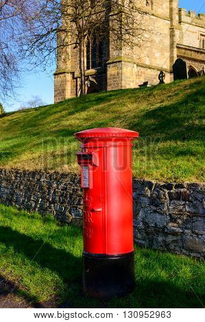 WYMESWOLD ENGLAND - JANUARY 15: A rural British red traditional Royal Mail pillar box. With St Mary's church - behind. In Wymeswold England on 15th January 2016.