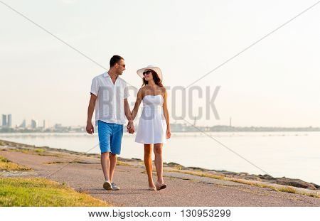 love, travel, tourism, summer and people concept - smiling couple on vacation wearing sunglasses and holding hands walking at seaside