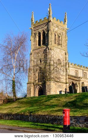 WYMESWOLD, ENGLAND - JANUARY 15: St Mary's Church, Wymeswold, with a British red traditional Royal Mail pillar box in foreground. In Wymeswold, England on 15th January 2016.