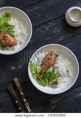 Rice chicken and salad in a bowl on a dark wooden background. Healthy delicious food