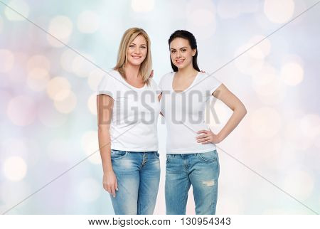 friendship, diverse, body positive and people concept - group of happy different women in white t-shirts hugging over holidays lights background
