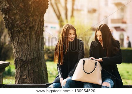 Two young adult women sitting in the street and looking for something in a bag