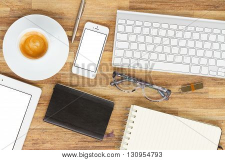 Office destop with black coffee, phone, tablet and keyboard, copy space on blank screen, top view