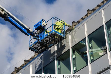 NOTTINGHAM ENGLAND - FEBRUARY 18: Two male construction workers working at height during building works on University Of Nottingham University Park campus. In Nottingham England. On 18th February 2016.