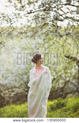 Happy young woman stands in the middle of a blossoming garden