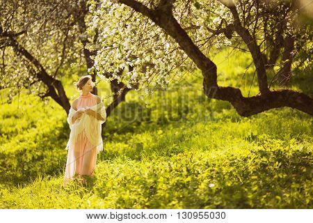 Happy beautiful young woman smelling a flower on an apple tree