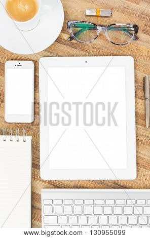 Flat lay wooden desktop with white tablet, copy space on blank screen