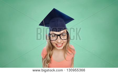 people, graduation and education concept - smiling young student woman in mortarboard and eyeglasses over green school chalk board background