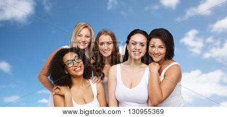 friendship, beauty, body positive and people concept - group of different happy women in white underwear over blue sky and clouds background