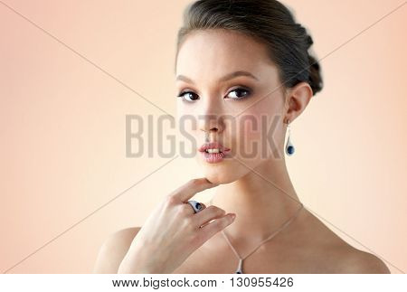 beauty, jewelry, people and luxury concept - beautiful asian woman or bride with earring, finger ring and pendant over beige background