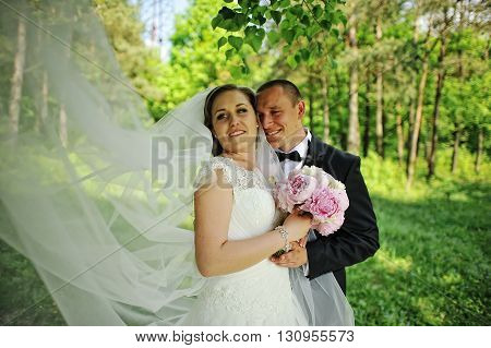 Beautiful Hugging Wedding Couple, Bride With Long Veil At Peony Bouquet At Hands
