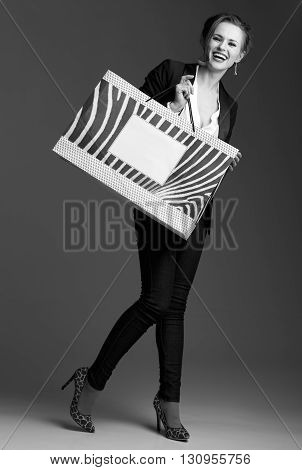 Happy Woman Showing Big Shopping Bag Against Grey Background