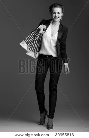 Smiling Woman With Big Shopping Bags Against Grey Background