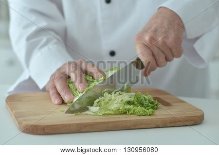 chef male hands cooking salad close up