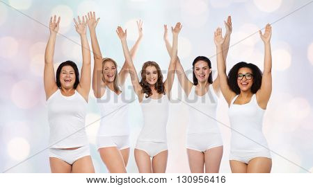 happiness, friendship, beauty, body positive and people concept - group of happy different women in white underwear with raised arms celebrating victory over holidays lights background
