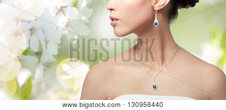 beauty, jewelry, wedding accessories, people and luxury concept - close up of beautiful asian woman or bride with earring and pendant over natural spring cherry blossom background