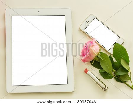 Styled flat desktop scene with white tablet, mobile and flowers