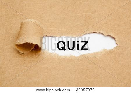 The word Quiz appearing behind torn brown paper.