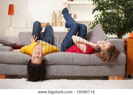 Happy teen girls resting on sofa at home, smiling.