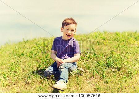 summer, childhood, leisure and people concept - happy little boy sitting on grass outdoors