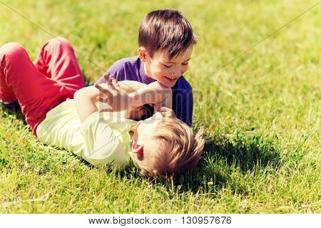 summer, childhood, leisure and people concept - happy little boys outdoors fighting for fun on green field