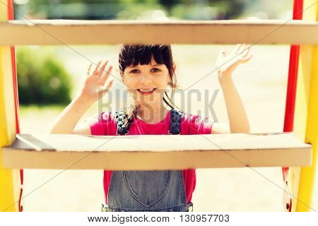 summer, childhood, leisure, gesture and people concept - happy little girl waving hand on children playground climbing frame