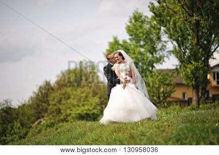 Gorgeous Wedding Couple On The Hill, Groom Kiss Bride
