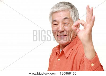 portrait of senior Japanese man showing perfect sign on white background
