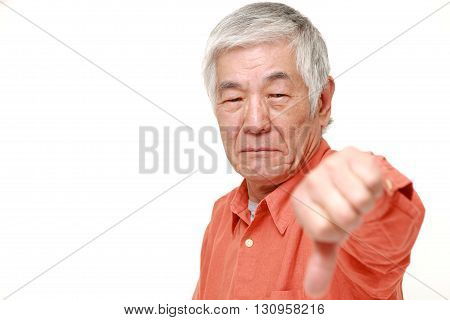 portrait of senior Japanese man with thumbs down gesture on white background