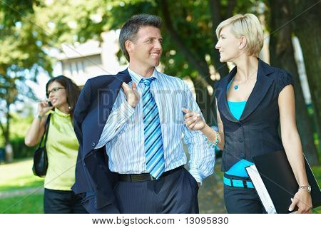 Businessman and businesswoman walking and talking in downtown park.
